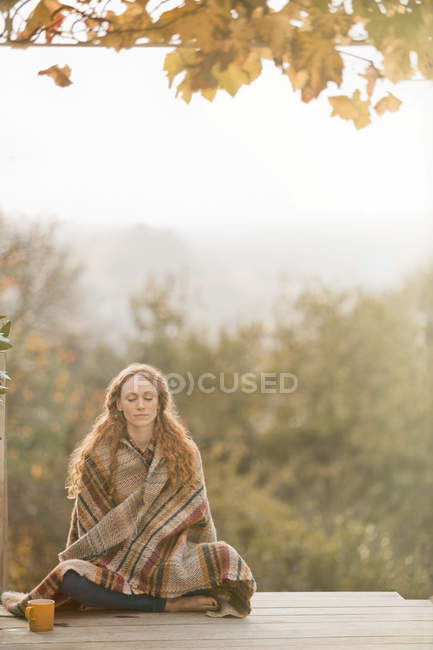 Serene woman wrapped in blanket meditating on autumn patio — Stock Photo
