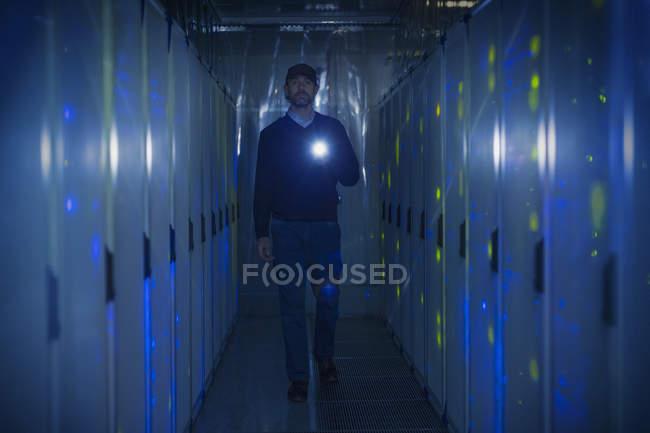 Сервер кімнаті технік з ліхтариком в темних коридор — стокове фото