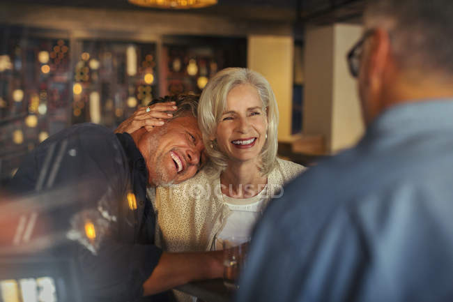 Affectionate senior couple laughing and hugging in bar — Stock Photo