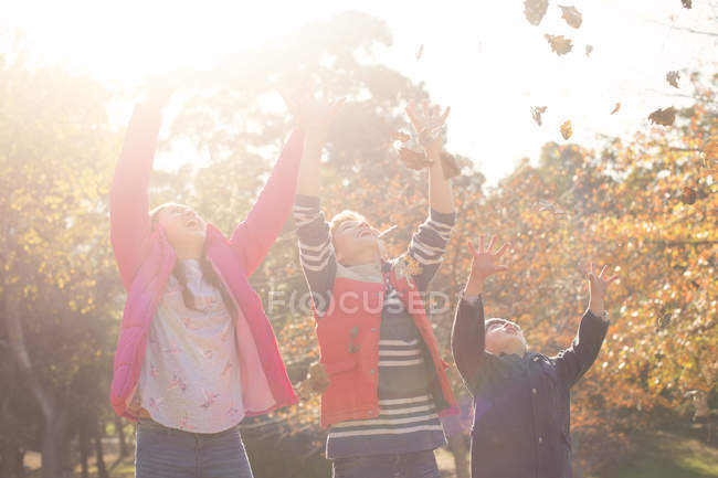 Boys and girl throwing autumn leaves overhead — Stock Photo