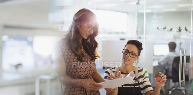 Creative businesswomen planning, discussing paperwork in office — Stock Photo