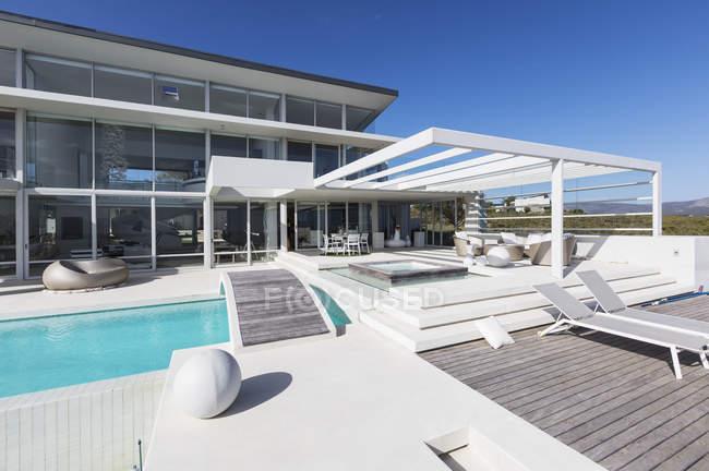 Солнечная современная витрина роскошного дома со стульями и бассейном — стоковое фото