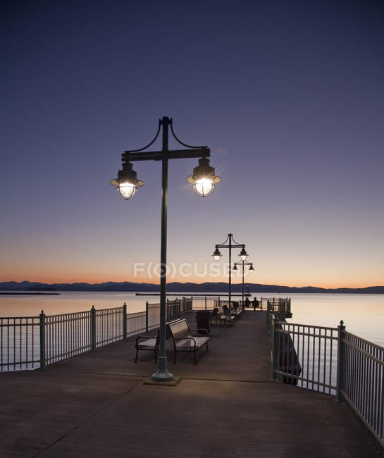 Tranquil pier at sunset over water — Stock Photo
