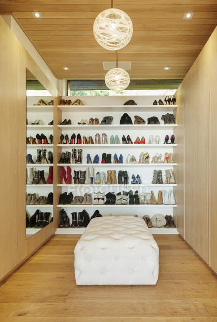 Modern walk-in closet with shoes on shelves — Stock Photo