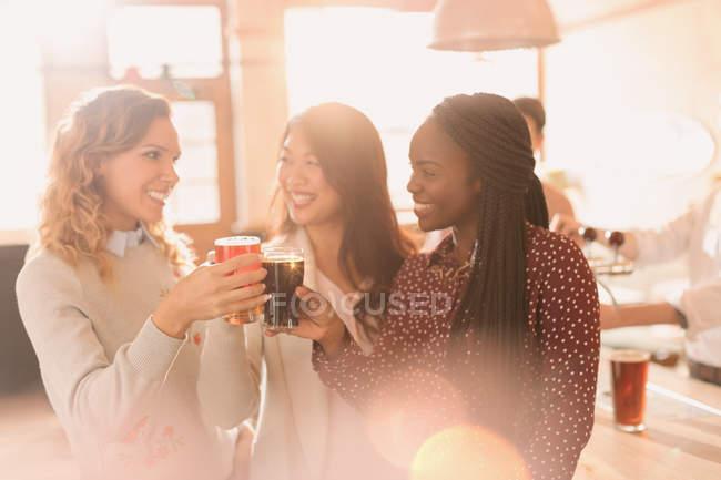 Amigos de mulheres brindando copos de cerveja no bar — Fotografia de Stock