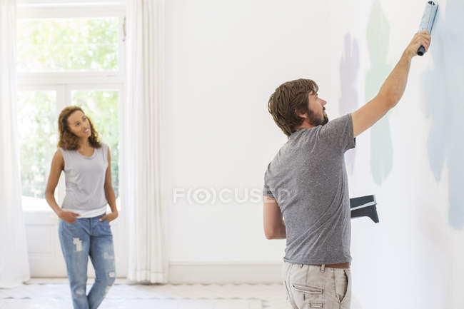 Man painting wall with girlfriend observing — Stock Photo