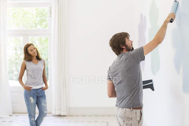 Uomo pittura parete con fidanzata osservando — Foto stock