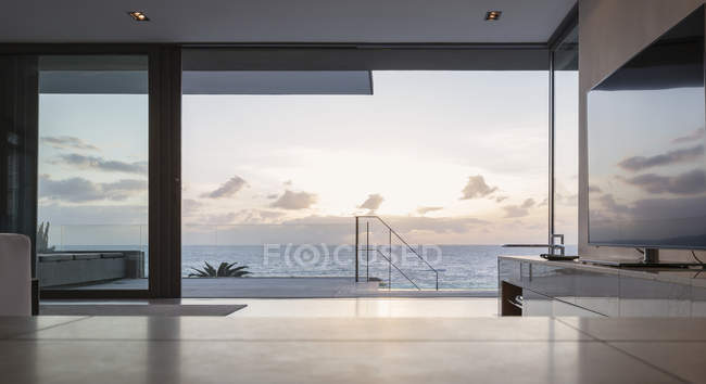 Home showcase living room and patio with tranquil sunset ocean view — Stock Photo