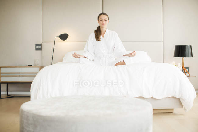 Serene woman in bathrobe meditating in lotus position on bed — Stock Photo