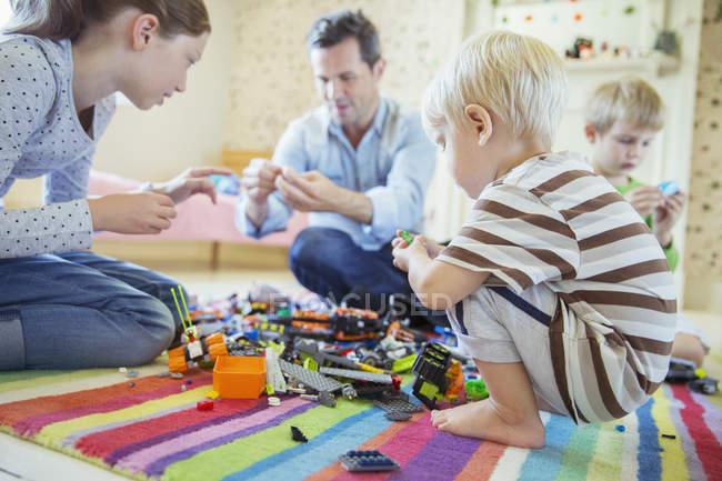 Padre jugando con niños - foto de stock