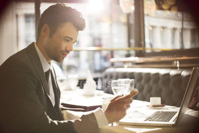 Young businessman using laptop in restaurant — Stock Photo