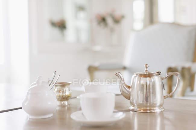Tasses et théière en argent sur la table — Photo de stock