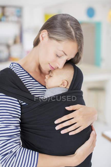 Мать Серена держит ребенка в слинге — стоковое фото