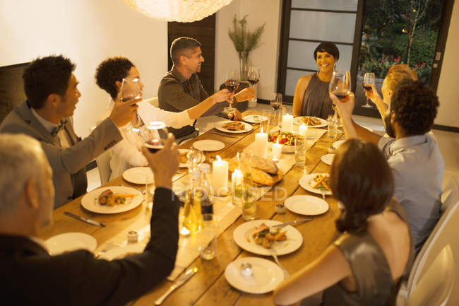 Friends toasting each other at dinner party — Stock Photo