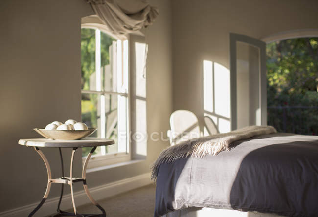 Sunny luxury bedroom against windows — Stock Photo