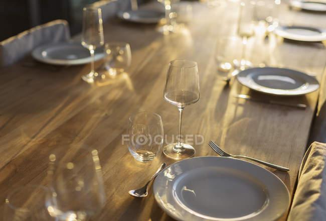 Reflexão ensolarado na placesettings na mesa de jantar de madeira — Fotografia de Stock