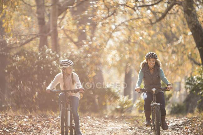Mère et fille vélo équitation sur le chemin dans les bois — Photo de stock