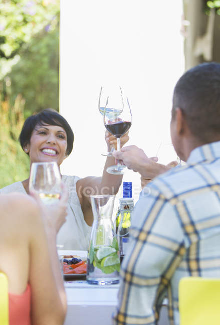 Friends toasting each other at table outdoors — Stock Photo