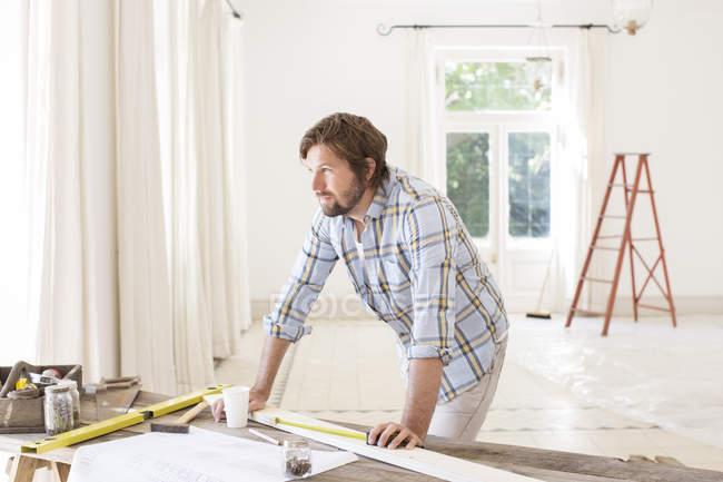 Человек с видом на строительный стол в жилом помещении — стоковое фото