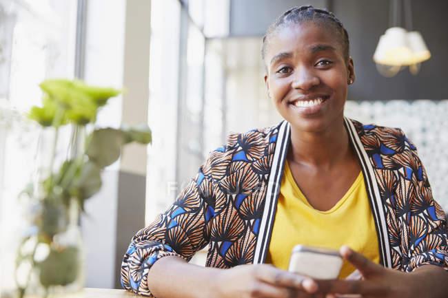 Ritratto donna d'affari sorridente che tiene il telefono delle cellule in caffè — Foto stock