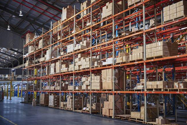 Boîtes en carton empilées sur des étagères dans un entrepôt de distribution — Photo de stock