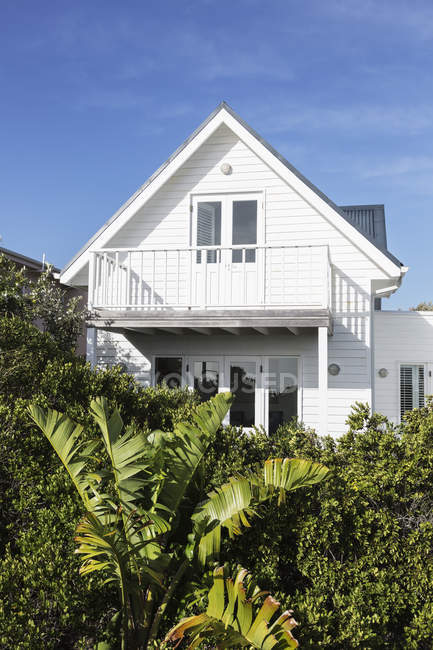 Balcony on white home showcase exterior beyond green hedge — Stock Photo