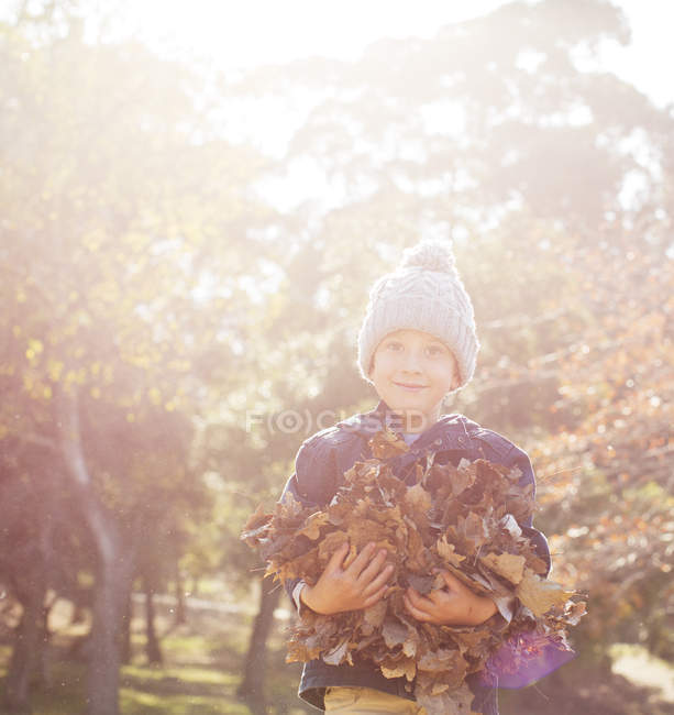 Porträt lächelnder Junge mit einem Strauß Herbstblätter — Stockfoto