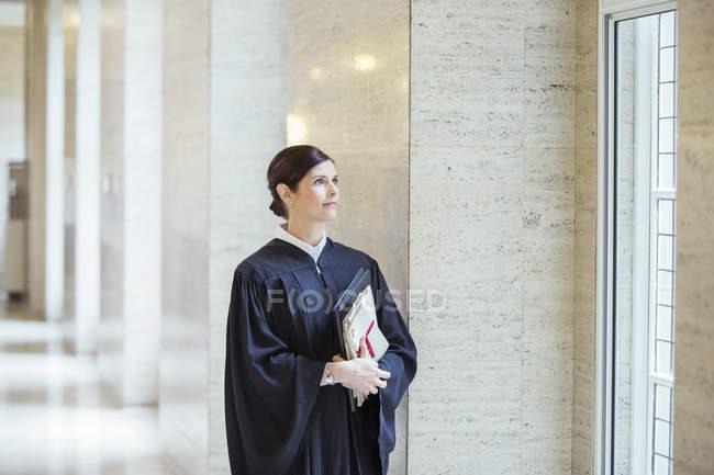 Судья смотрит в окно в здании суда — стоковое фото