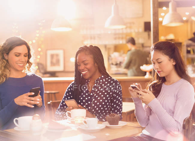 Mensagens de amigos mulheres com celulares na mesa de café — Fotografia de Stock