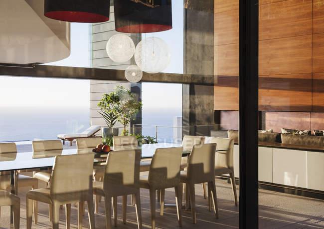Table et chaises dans la salle à manger moderne donnant sur l'océan — Photo de stock