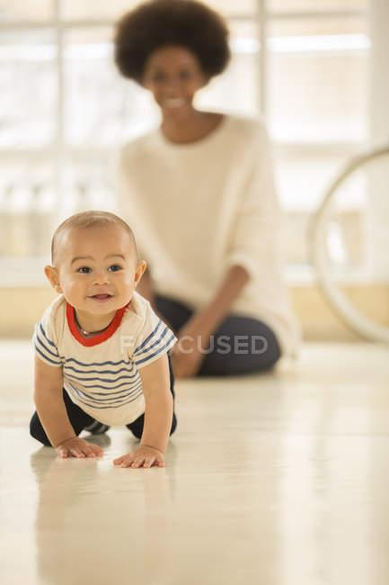 Mutter beobachtet Baby zu Hause auf dem Boden kriechen — Stockfoto
