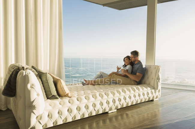 Affectionate couple drinking wine on tufted chaise lounge with ocean view — Stock Photo