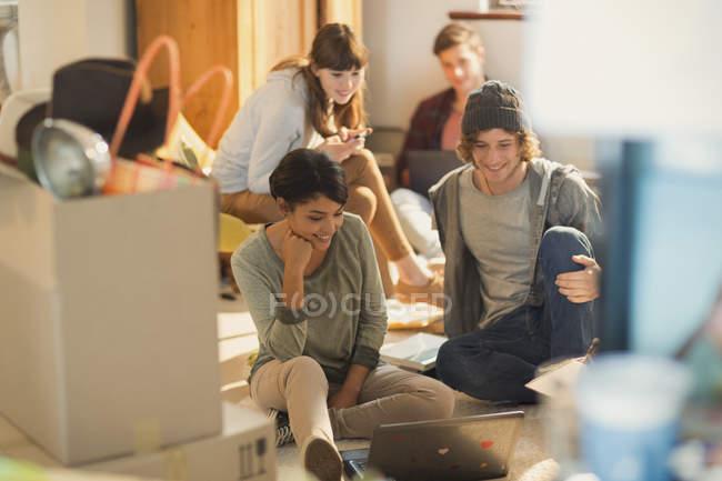 Coppie giovani compagni di stanza usando il portatile disimballaggio scatoloni in nuovo appartamento — Foto stock