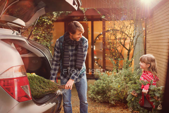 Father and daughter unloading Christmas tree from car outside house — Stock Photo
