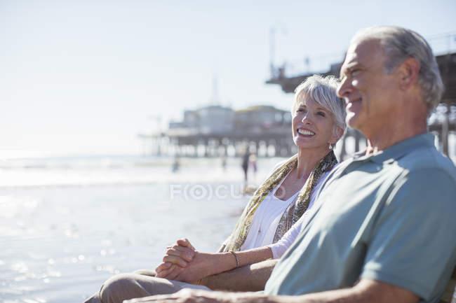 Pareja mayor relajándose en la playa soleada - foto de stock