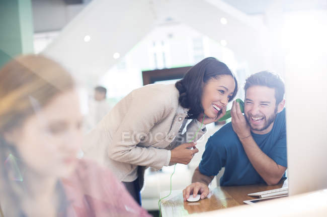 Creative business people sharing and listening to headphones in office — Stock Photo