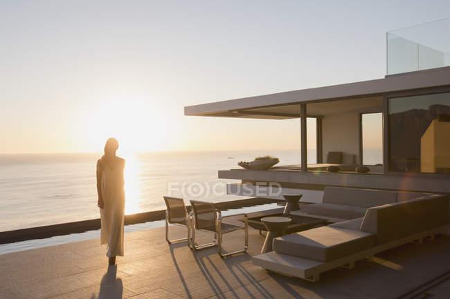 Mujer caminando en la moderna, casa de lujo escaparate terraza exterior con vista al mar puesta de sol - foto de stock