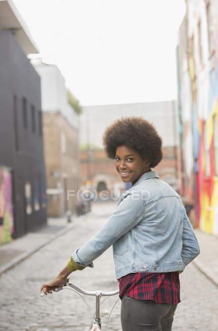 Жінка, штовхаючи велосипед на місто вулиці — стокове фото