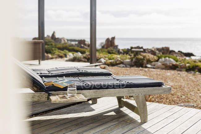 Book and water at lounge chair on patio overlooking ocean — Stock Photo