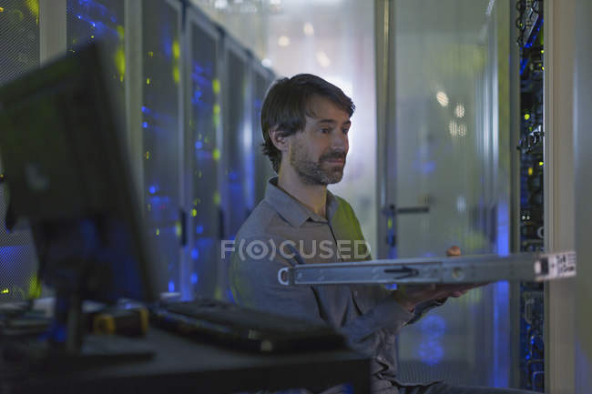 Server room technician removing rack from cabinet panel — Stock Photo