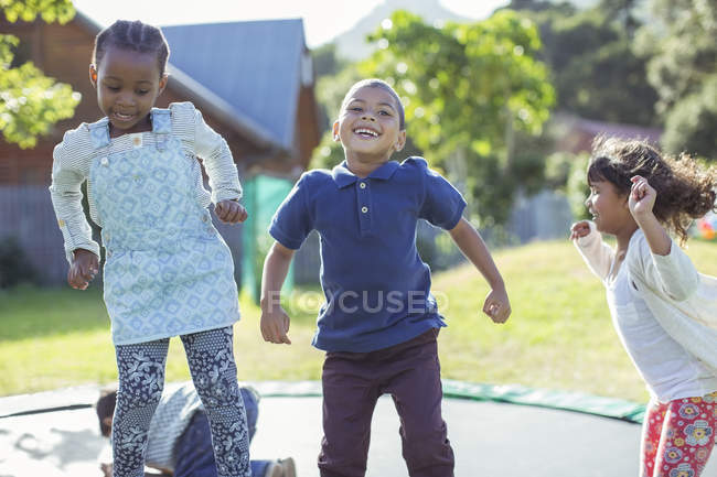 Children jumping on trampoline outdoors — Stock Photo