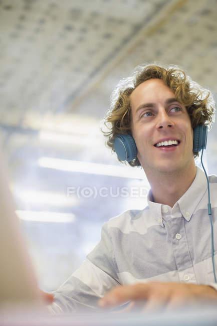 Glücklicher junger Geschäftsmann hört Kopfhörer im Büro — Stockfoto