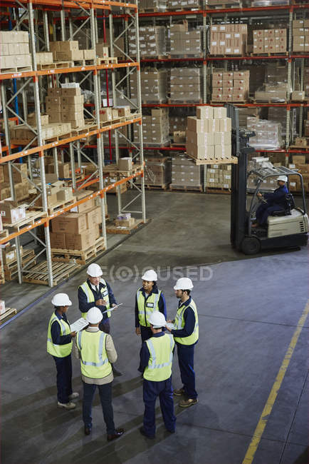 Manager and workers meeting in circle in distribution warehouse — Stock Photo