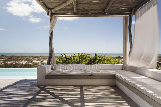 Luxury poolside patio overlooking ocean — Stock Photo