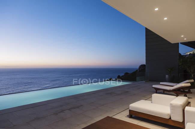 Современный внутренний дворик и бассейн с видом на океан на закате — стоковое фото