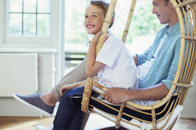 Father and son sitting in wicker chair — Stock Photo