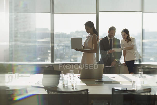 Business people working, using laptop and digital tablet in sunny conference room meeting — Stock Photo