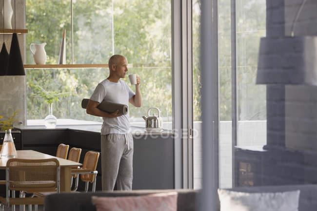 Uomo maturo con stuoia di yoga bere caffè in cucina — Foto stock
