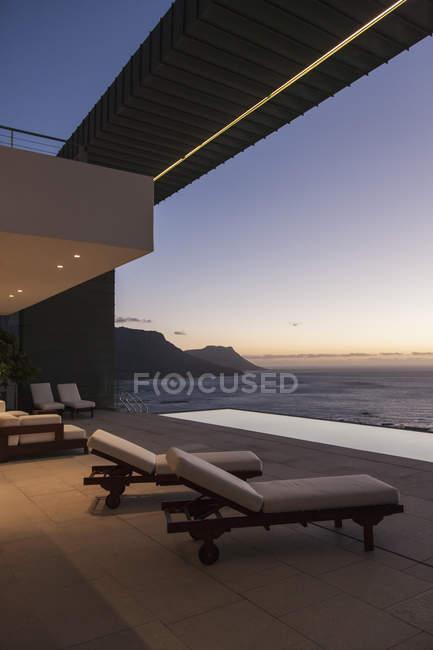 Балкон з видом на океан сучасний будинок на заході сонця — стокове фото