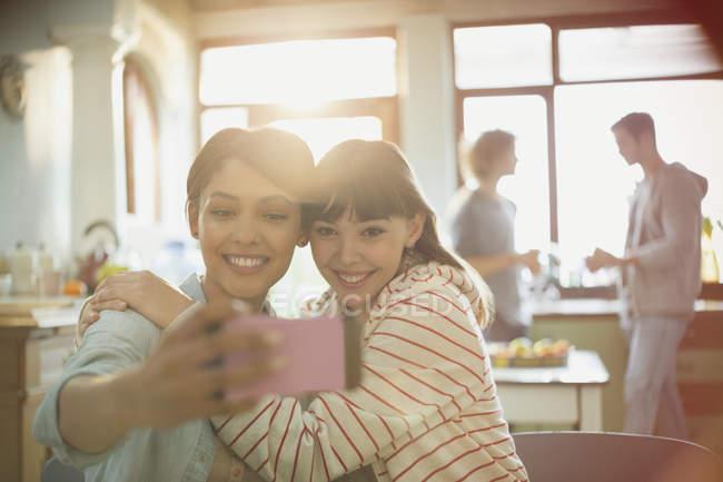 Coinquilini gli amici delle giovani donne che abbraccia selfie di scattare con la fotocamera del telefono — Foto stock
